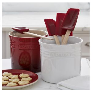 white and red stoneware utensil holders; white one holds spatulas