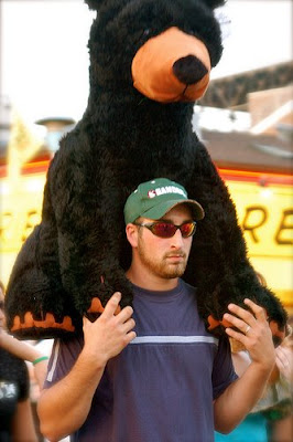 man with giant stuffed plush bear on his shoulders, a prize won at a state fair