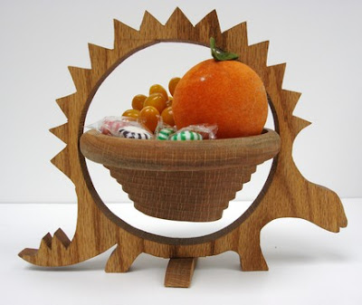 wood basket in a wood frame shaped like a stegosaurus