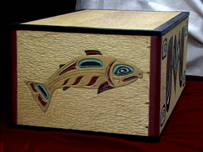 intricately carved bentwood box with raven and dog salmon