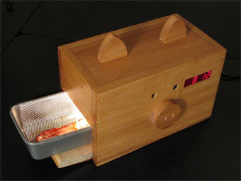 wake n; bacon alarm clock, shaped like a pig, with place to cook bacon