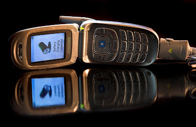 free stock photo of a flip cell phone open, and showing charging in the lit up screen, copyright J. Gracey Stinson