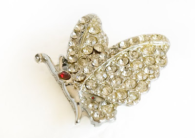 silver plated vintage brooch in the shape of a butterfly and covered with rhinestones