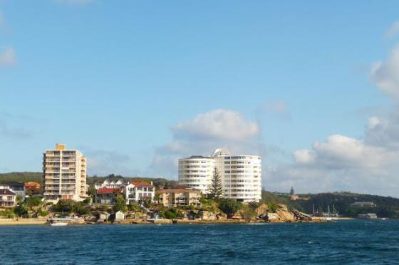 Aquí una vista de los edificios al lado del mar en Sydney