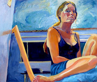Seated self portrait oil painting in studio at night.