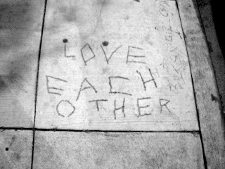 Love Each Other written in the sidewalk