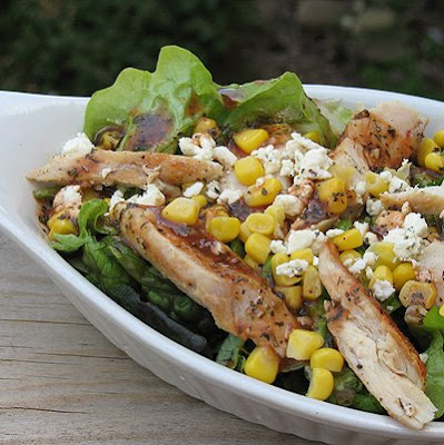A close up photo of a grilled chicken salad with herbed tomato vinaigrette in a white bowl.