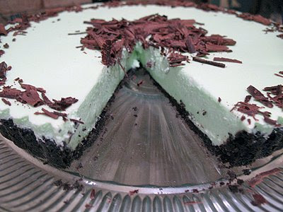 A close up photo of a grasshopper pie on a clear cake stand with a slice missing.