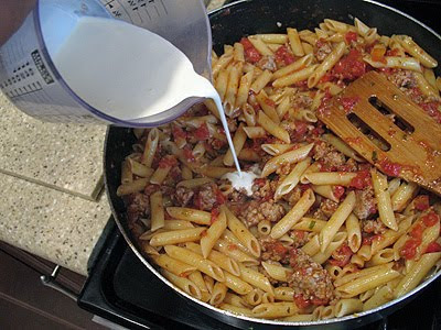 A photo of cream being added to the penne and sauce mixture in a large saute pan.