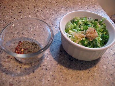 A close up photo of a bowl of seasonings and another bowl of shallots and garlic.