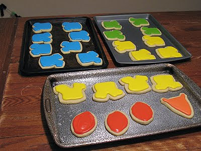 A photo of sheet pans of football and jersey shaped cookies with colored frosting on top.