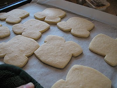 A close up photo of football jersey shaped cookies on a pan with parchment paper.