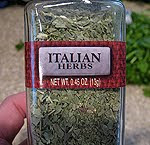 A close up photo of a jar of Italian herbs.