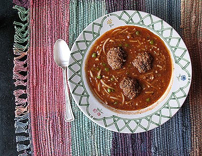 An overhead photo of a bowl of Amanda\'s meatball soup with a spoon resting on the side.