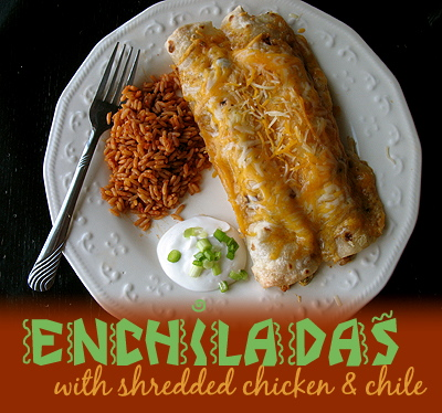 An overhead photo of shredded chicken and Chile enchiladas on a white plate with Spanish rice and sour cream on the side.