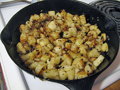 A skillet filled with cubed potatoes.