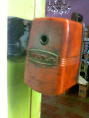 An orange beat-up pencil sharpener is affixed to a wall.
