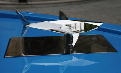 stainless steel shark scupture atop the RAl 5015 boat