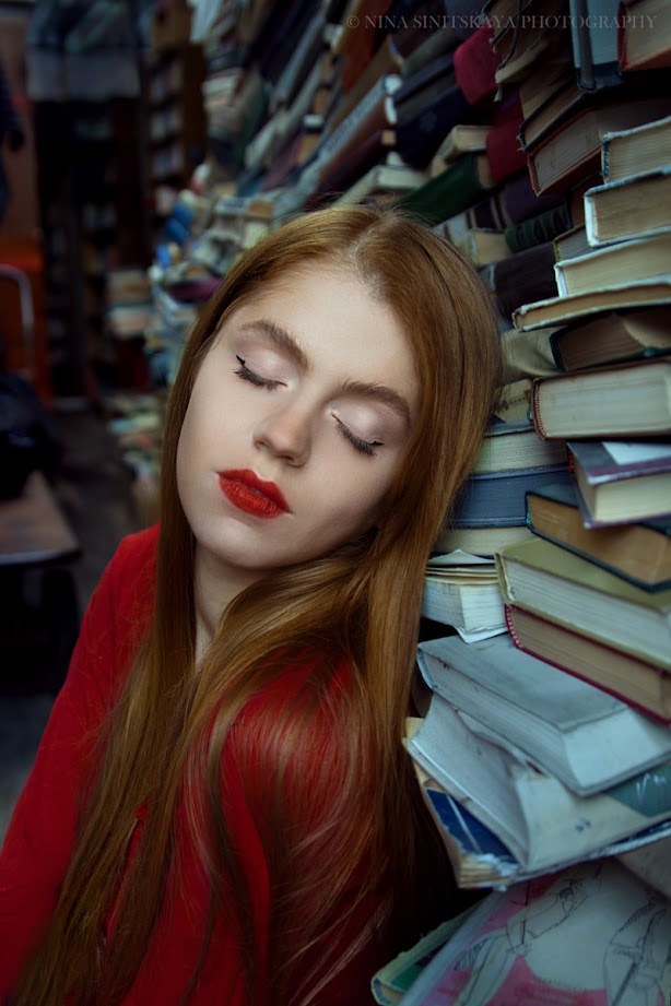 Portrait of woman with red hair and lips among the books